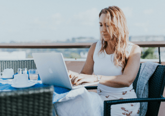 A woman working from a balcony: remote workers salaries