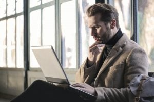 A businessman staring at his laptop at the airport